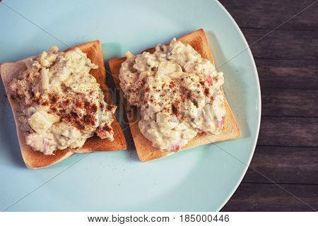 Two sandwiches with avocado salad on blue plate. Crunchy toast with vegetarian salad. Avocado and mayonnaise with egg and paprika. Healthy breakfast. Vegetarian fast-food. Guacamole with bread snack