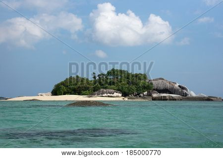 Small Island With White Sand Beach And Natural Granite Rock Formation And Green Vegetation Surrounde