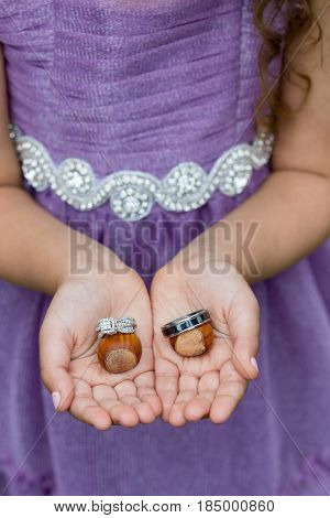 Flower girl ring bearer holding wedding rings on filbert nuts at an outdoor orchard wedding in Oregon.