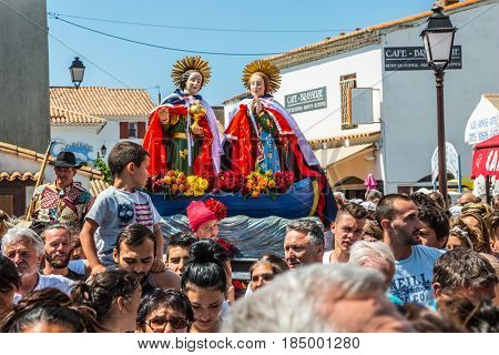 Saintes-Maries-de-la-Mer, France - May 25, 2015. Religious feast in honor of the Holy Maries in Provence. The concept of ethnographic tourism. Christians accompany two statues of the Holy Mary