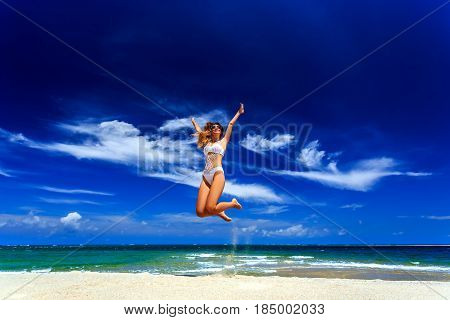 Model In White Bikini Jumping At The Beach