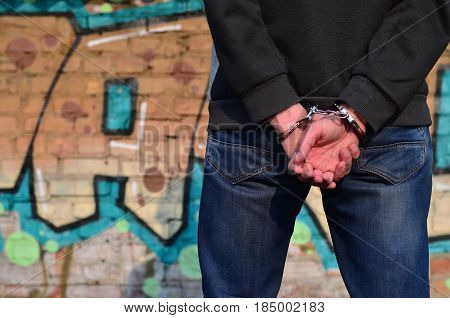 Rear View Of The Arrested And Handcuffed Offender Against The Graffiti Background
