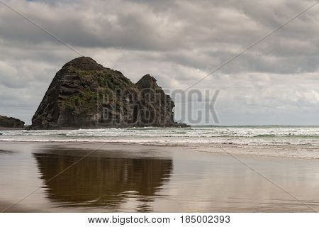 Auckland New Zealand - March 2 2017: Closeup of Rabbit rock is mirrored on wet sandy Piha Beach under stormy sky and surrounded by Tasman Sea surf.