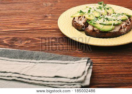 Open avocado sandwiches with tuna on whole grain bread against a dark background