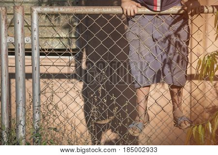 Child climbs over a wire fence with selective and soft focus.