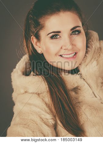 Happy attractive woman wearing light furry warm cozy coat with hood perfect for winter. Cold days fashion concept.