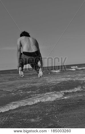 Young Man is jumping in a beautiful Beach