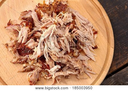 Pulled pork on rowmn wooden board. Top view