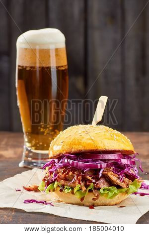 Sandwich with pulled pork and vegetables and glass of beer on wooden background