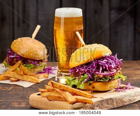 Two sandwiches with pulled pork, french fries and glass of beer on old wooden background. Rustic style