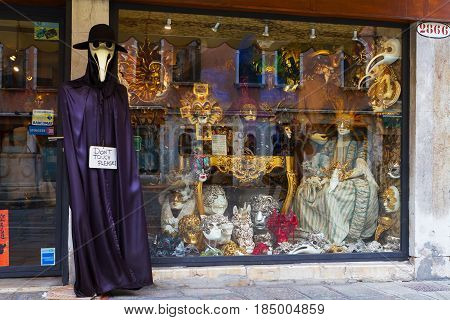 VENICE-JANUARY 12 2017. Different carnival masks in a showwindow of souvenir store and a manikin dressed in a plague doctor costume behind it. January 12 Venice Italy.