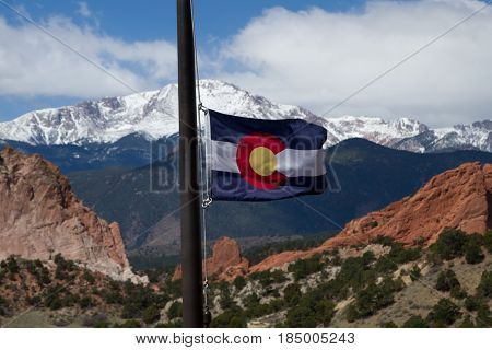 Colorado State Flag with Pikes Peak and Garden of the Gods in the background on a spring day