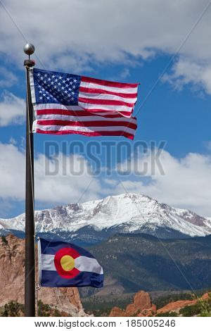 American and Colorado Flag waving in the wind with Pikes Peak and Garden of the Gods in the background