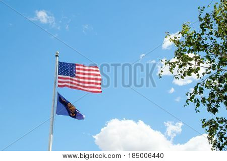 United States and the State of Oregon flags together on a flag pole.