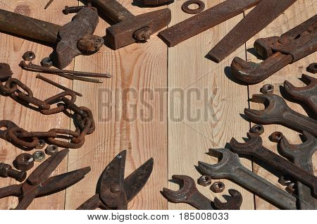 A Set Of Old And Rusty Tools Lies On A Wooden Table In The Workshop