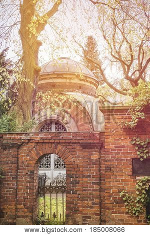 Red Brick Wall With Gate, In Front Of An Old Tomb