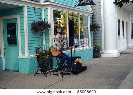 HARBOR SPRINGS, MICHIGAN / UNITED STATES - AUGUST 4, 2016: Musicians perform in front of Mary Ann Archer's fine jewelry store at the Street Musique event in downtown Harbor Springs.