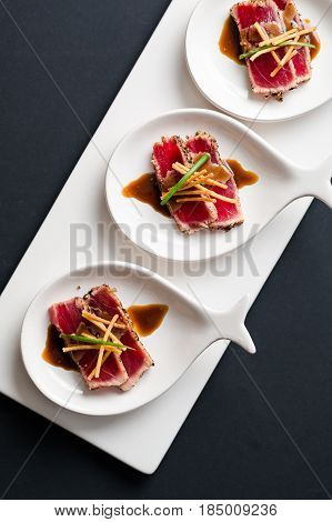 Tuna Tataki Top View. Tuna Tataki is a Japanese dish which consist of briefly seared tuna steak in thin slices. Served as appetizer with brandy sauce and garnish on a dark background.