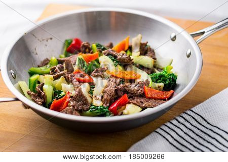 Beef Stir Fry in a wok. Healthy vegetable & beef stir-fry. Made with flank steak peppers onions and bok choy stir fried in an asian wok.