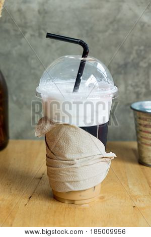 Iced coffee with straw in plastic cup on wood table
