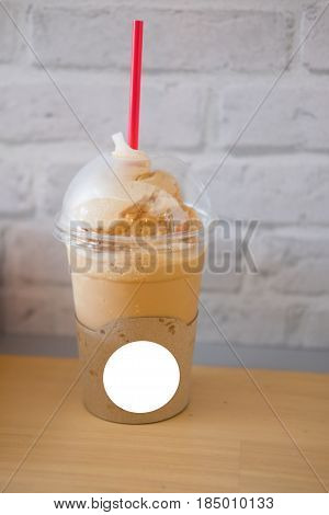 ice coffee frappe with red straw in plastic cup on wood table