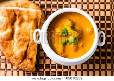 Butter chicken top view. Delicious butter chicken served in a white bowl with naan bread and rice on the side on a wooden place mat viewed from above.