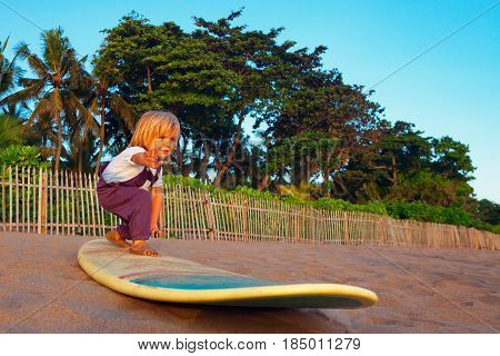 Little baby boy - young surfer stand on surf board with fun on sunset sea sand beach. Family lifestyle people outdoor water sport lessons and swimming activity on summer surf camp vacation with child