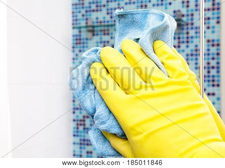 Person doing chores in bathroom at home cleaning mirror with microfiber towel