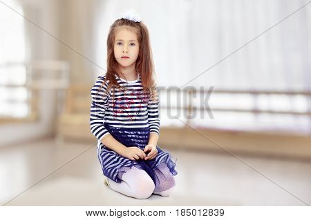 Beautiful little girl long hair and white bow on her head , in a summer dress in stripes.She kneels on the floor.In the room with the big bright window in the wall.