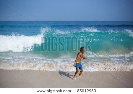 Handsome muscular curly blond wet man in a blue shorts and with naked fit torso is looking at the big wave rising behind him and ready to run away from danger