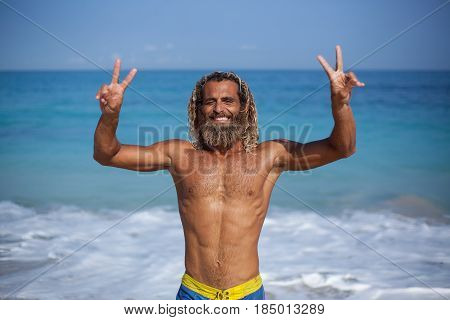 Half-length horizontal portrait of an handsome muscular bearded curly wet man with naked fit torso standing front of the ocean with hands up smiling and holding his fingers in a sign of victory