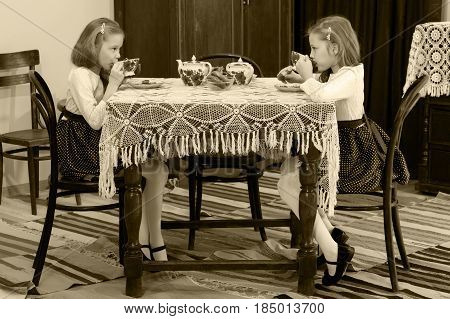 Cute little girls twins drinking tea at an antique table with a lace tablecloth.Black-and-white photo. Retro style.