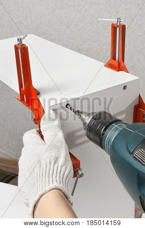 hands drilling a hole during assembling of furniture