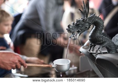 metal dragon spewing water in the well in the Senso-ji temple Tokyo Japan.