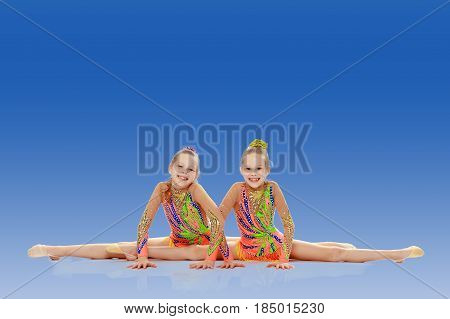 Two adorable little twin girls, gymnastics in the sports school. Girls beautiful gymnastic leotards. They do the splits.On a bright blue gradient background.