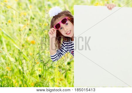 The little blonde girl with long hair and with a white bow on her head , in a blue striped summer dress.The girl in the dark sunglasses peeking from behind the banner.Summer white green blurred background.