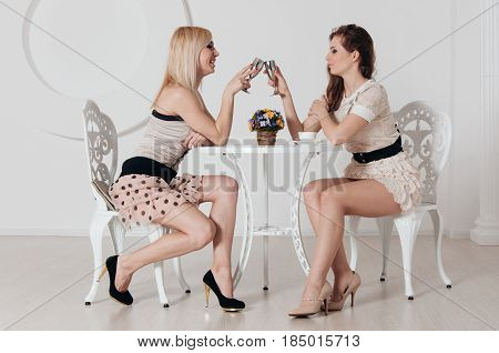 Two Incredible Girls Are Sitting At The Table