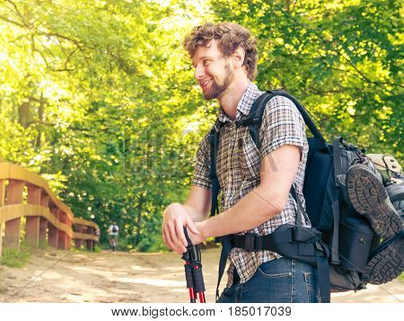 Adventure tourism enjoying summer time - young tourist man with backpack sticks hiking in forest trail