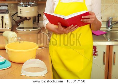 Creative housewife planning dinner supper. Part body woman chef with cookbook in house kitchen.