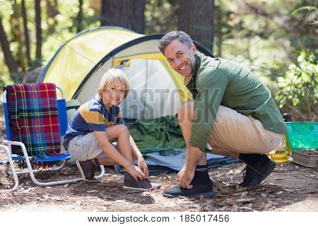 Portrait of smiling father and son tying shoelace by tent at campsite