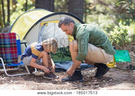Side view of father and son tying shoelace by tent at campsite