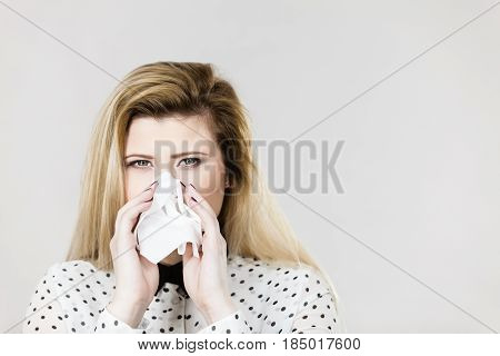 Sickness seasonal virus problem concept. Woman being sick having flu sneezing into tissue