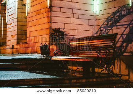 Beautiful Wrought iron bench made of wood in the rain. Night autumn landscape of urban architecture. Art processing: