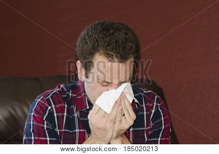 Sick man blowing his nose into a tissue.