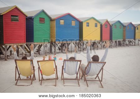 Family with arms raised resting on lounge chairs at beach