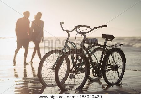 Bicycles parking on shore with couple in background at beach during sunny day