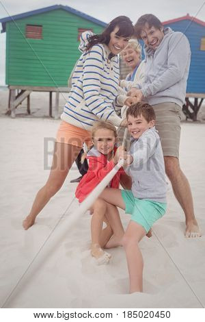 Happy multi-generation family playing tug of war at beach