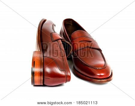 Pair of leather burgundy penny loafer shoes together on white background. One shoe on side. Horizontal image