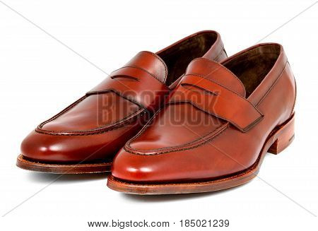 Pair of leather burgundy penny loafer shoes together on white background. Horizontal image diagonal left