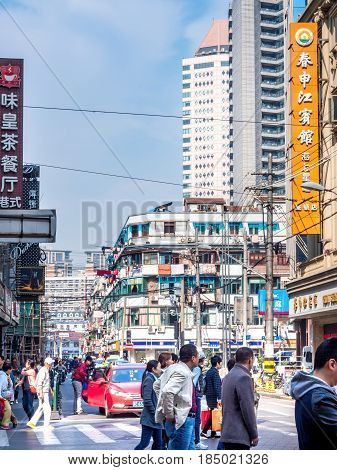 Shanghai, China - Nov 4, 2016: Along Nanjing Road Pedestrian Street - Crowds and traffic at the intersection of Wufu Long Road. This forms part of Old Shanghai.